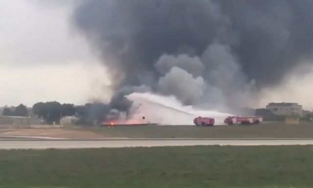 Na snímke z videa hasiči hasia plamene a dym stúpajúci z miesta zrútenia ľahkého lietadla po štarte na medzinárodnom letisku vo Vallette na Malte
