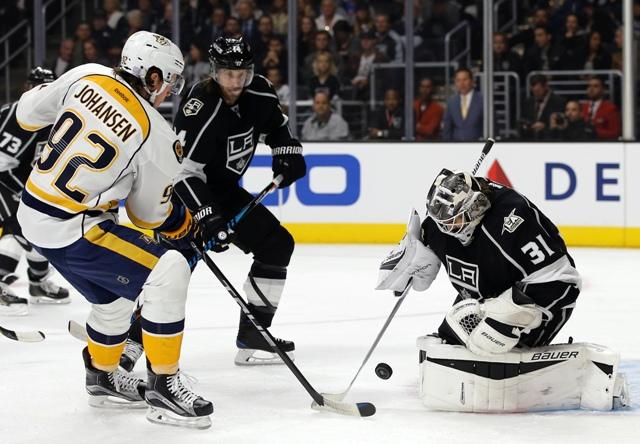 Hokejista Nashville Predators  Ryan Johansen (vľavo),  brankár Los Angeles Kings Slovák Peter Budaj (vpravo) a jeho spoluhráč Tom Gilbert v zápase zámorskej hokejovej NHL Los Angeles Kings  - Nashville Predators