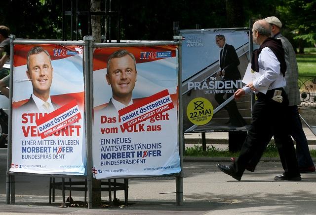 Ľudia kráčajú okolo plagátov prezidentských kandidátov Norberta Hofera (vľavo) z pravicovej populistickej Slobodnej strany Rakúska (FPÖ) a jeho súpera, bývalého šéfa rakúskych Zelených Alexandra Van der Bellena