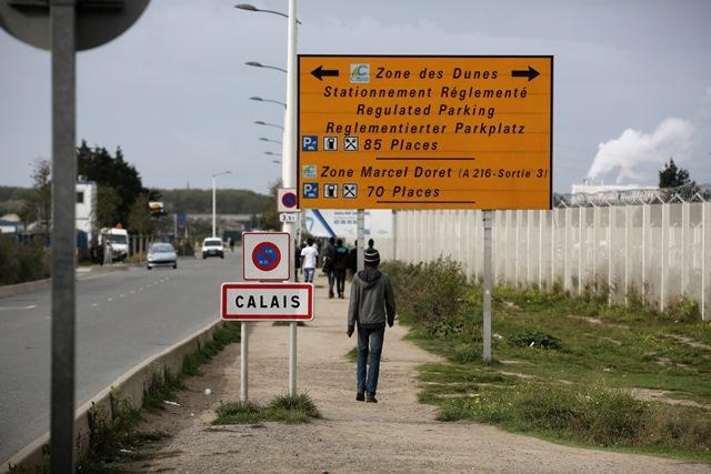 Migranti kráčajú pred táborom  zvaného Džungľa