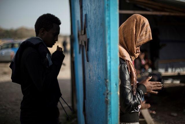 Migranti sa modlia počas poslednej bohoslužby v provizórnom kostole v tábore Džungľa pri Calais