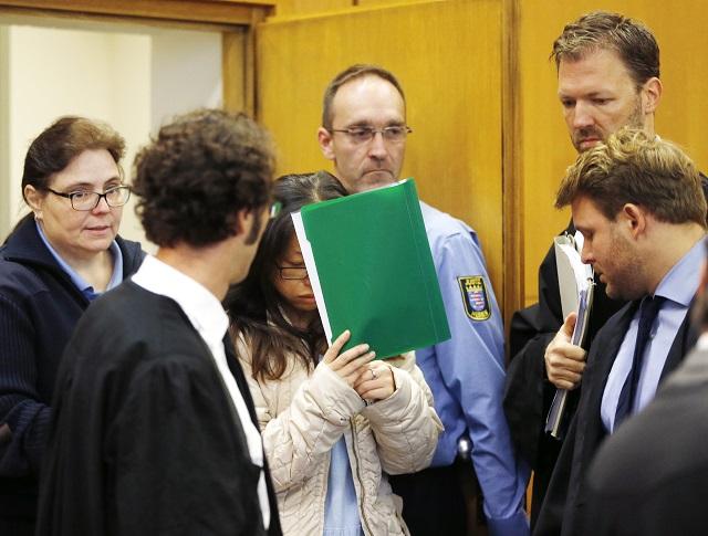 Juhokórejčanka si zakrýva tvár na súde vo Frankfurte 10. októbra 2016. äť Juhokórejčanov predstúpilo dnes pred mestský súd v nemeckom meste Frankfurt nad Mohanom. Proces sa týka vlaňajšej vraždy príbuznej počas rituálu exorcizmu v hotelovej izbe vo Frankfurte, píše agentúra AP. Medzi obžalovanými vo veku od 16 do 44 rokov je aj syn 41-ročnej obete rituálu
