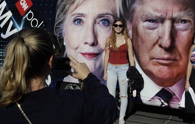 Na archívnej snímke študentky pózujú pred fotografiami kandidátov na prezidenta USA -  demokratky Hillary Clintonovej  a republikána Donalda Trumpa pred ich duelom