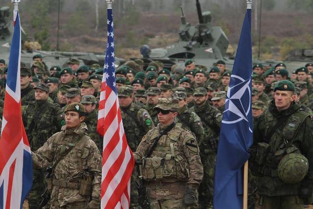 Na snímke vojaci s vlajkami NATO, USA a Veľkej Británie