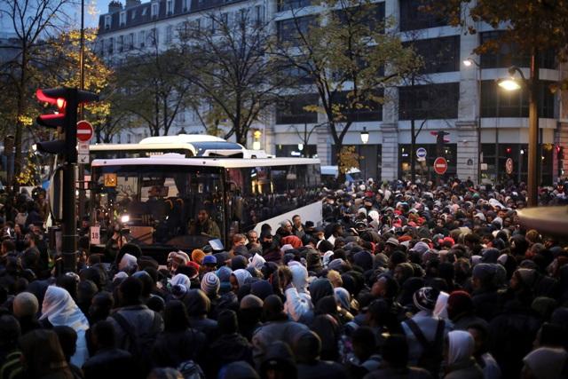 Migranti čakajú na nastúpenie do autobusov, ktoré ich odvezú do dočasných prístreškov 4. novembra 2016 v Paríži