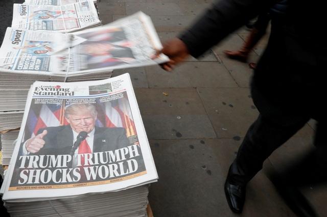 """Chodci prechádzajú okolo novín Evening Standard s titulkom """" Trumpov triumf šokoval svet"""" v Londýne"""