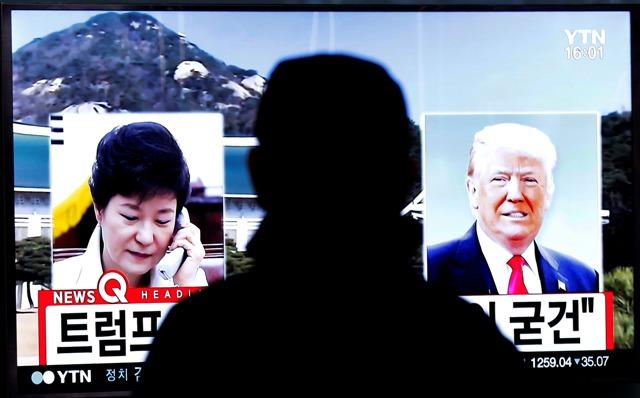 Muž sa pozerá na televíznu obrazovku, na ktorej sú podobizne budúceho amerického prezidenta Donalda Trumpa a juhokórejskej prezidentky Pak Kun-hje