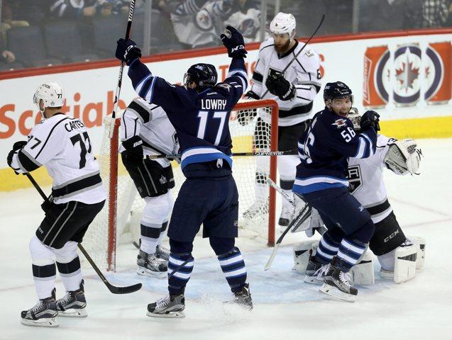 Hráč Winnpegu Jets Adam Lowry (17) sa raduje z gólu so spoluhráčom Markom Daňom do brány Petra Budaja z LA Kings v zápase hokejovej NHL Winnipeg Jets - Los Angeles Kings