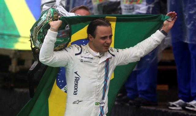 Na snímke brazílsky pilot formuly 1 Felipe Massa z tímu Williams nesie brazílsku vlajku, čo musel odstúpiť z pretekov po havárii na Veľkej cene Brazílie v Sao Paule