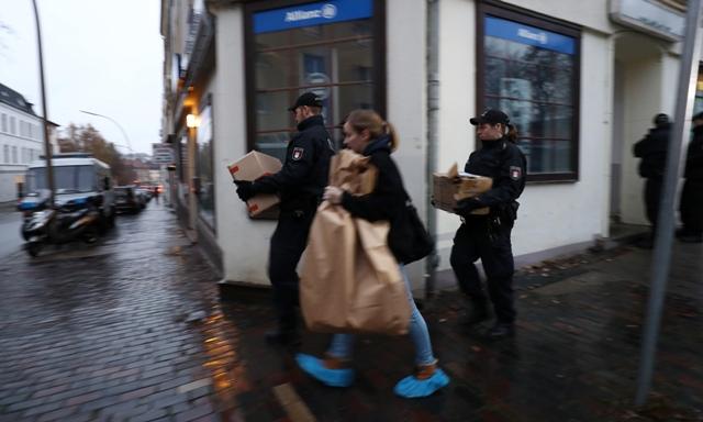 Policajti nesú škatule z mešity počas razie 15. novembra 2016 v Hamburgu