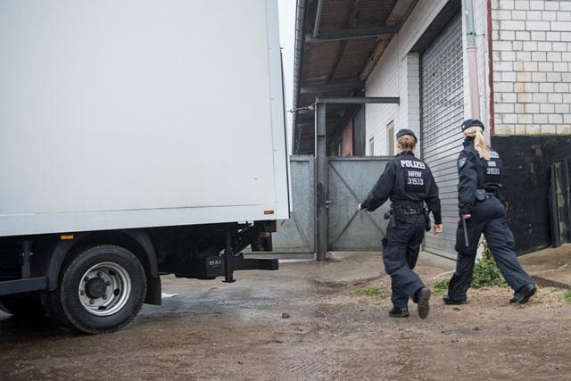 """Policajti vchádzajú do skladovacích priestoroch """"Lies! Verlag Gesellschaft"""" v nemeckom Pulheime neďaleko Kolína nad Rýnom 15. novembra 2016"""
