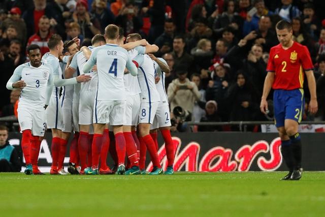 Na snímke vpravo Cesar Azpilicueta (Španielsko) prechádza okolo radujúcich sa hráčov Anglicka po úvodnom góle Adama Lallanu v prípravnom medzištátnom zápase Anglicko - Španielsko