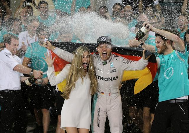 Nemecký pilot F1 na Mercedese Nico Rosberg oslavuje na pódiu s manželkou Vivian Siboldovou po tom, ako sa stal majstrom sveta Formuly 1 po pretekoch nedeľňajšej Veľkej ceny Abú Zabí na okruhu Yas Marina v Abú Zabí