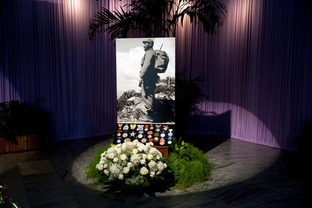Na snímke medaily a kvety sú pred čiernobielym portrétom zosnulého Fidela Castra