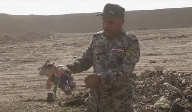 Na snímke z videa iracký policajt drží v ruke vypchatú hračku na mieste nálezu masového hrobu v meste Hamám al-Alíl, južne od irackého mesta Mósul