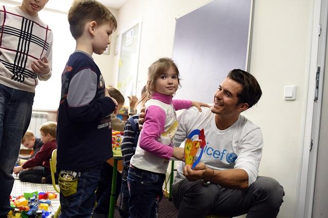 Na snímke z 27. apríla 2016, ktorú organizácia UNICEF poskytla 4. mája, vyslanec dobrej vôle Detského fondu OSN (UNICEF) a britský herec Orlando Bloom sa zdraví so štvorročným dievčatkom v komunitnom centre v meste Sviatogorsk na východe Ukrajiny