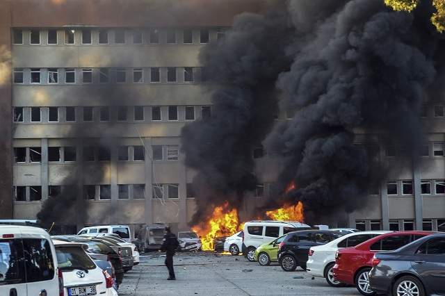 Policajt kráča okolo horiaceho auta po výbuchu, ku ktorému došlo na parkovisku pred vládnou budovou v juhotureckom meste Adana vo štvrtok v skorých ranných hodinách 24. novembra 2016