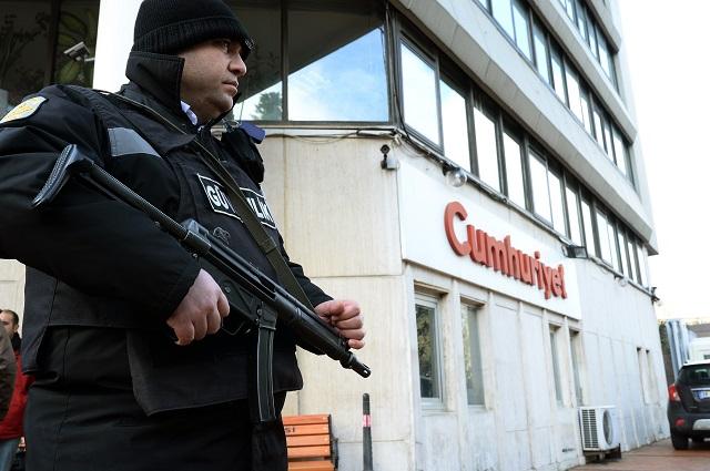 Policajt hliadkuje pred vstupom do budovy tureckého denníka Cumhuriyet