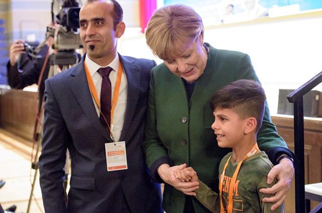 Na snímke nemecká kancelárka Angela Merkelová (uprostred) a malý Afganec Edris sa držia za ruku na zjazde Merkelovej Kresťanskodemokratickej únie (CDU)