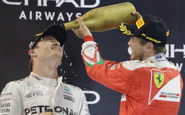 Nemecký pilot F1 na Mercedese Nico Rosberg (vľavo) oslavuje na pódiu s tretím Nemcom Sebastianom Vettelom, ktorý ho sprejuje šampanským po tom, ako sa stal majstrom sveta Formuly 1