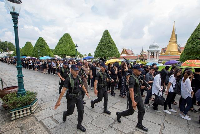Thajskí vojaci kráčajú okolo smútiaceho davu v čiernom, ktorý prichádza vzdať hold zosnulému thajskému kráľovi