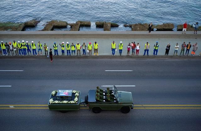 Na snímke ľudia lemujú cestu, na ktorej vojenské auto vezie urnu s popolom kubánskeho lídra Fidela Castra pokrytú kubánskou zástavou počas jazdy ulicami Havany