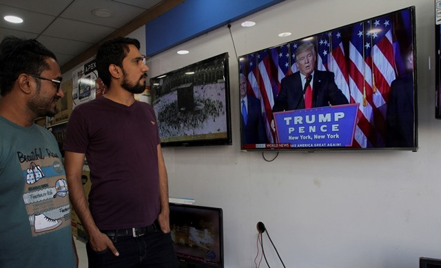 Na snímke muži sa dívajú na obrazovku, na ktorej je Donald Trump