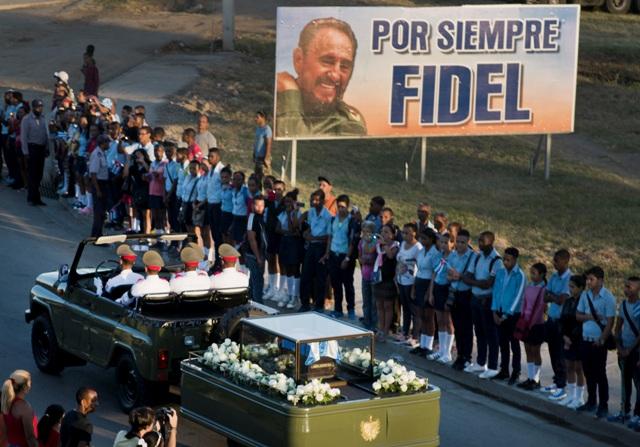 Vojenské auto vezúce urnu s popolom kubánskeho lídra Fidela Castra pokrytú kubánskou zástavou smeruje na pohreb na cintorín sv. Ifigénie v Santiagu de Cuba 4. decembra 2016