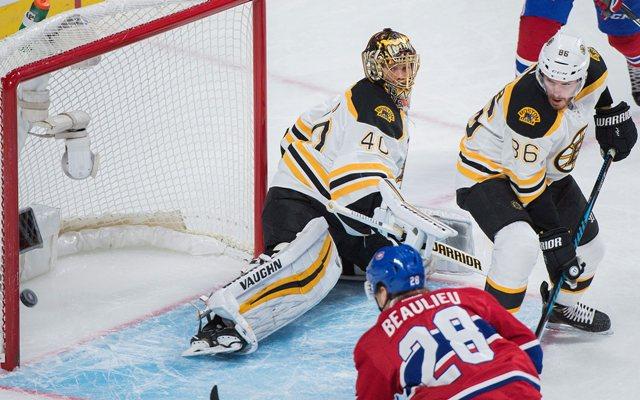 Brankár Bostonu Tuuka Rask je prekonaný po teči hráča Canadiens Nathana Beaulieua (vpravo dole) v zápase zámorskej NHL Boston Bruins - Montreal Canadiens