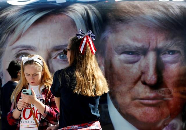 Ilustračné foto: Dievčatá telefonujú pred autobusom s pútačom na prvú priamu debatu prezidentských kandidátov Hillary Clintonovej a Donalda Trumpa