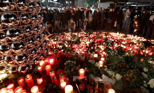 Ľudia zapaľujú sviečky neďaleko vianočného trhu 21. decembra 2016 v Berlíne