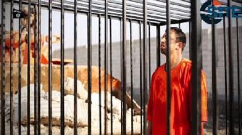 Na archívnej snímke z videozáznamu  z roku 2015 zverejneného extrémistami z tzv. Islamského štátu (IS) je jordánsky pilot Muáza Kasásbu v klietke pred upálením