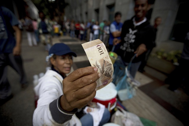 Pouličný predavač kontroluje pravosť 100-bolívarovej bankovky pred bankou v Caracase 13. decembra 2016. Hospodárska kríza vo Venezuele vyhnala mieru inflácie na rekordnú úroveň, najvyššiu na svete. Podľa odhadu nezávislých odborníkov do konca tohto roka sa inflácia v krajine vyšplhá na úroveň 600 - 700 %. Venezuelská mena sa tak stala takmer bezcenná