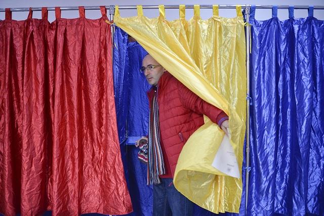Muž vychádza spoza plenty vo farbách rumunskej trikolóry vo volebnej miestnosti v rumunskej Bukurešti