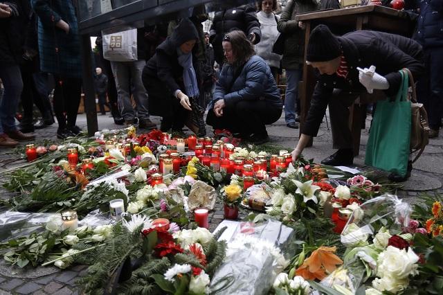 Ľudia kladú kvety neďaleko miesta v utorok 20. decembra 2016, kde nákladné auto v pondelok narazilo do davu ľudí na vianočných trhoch v Berlíne. Dvanásť osôb zahynulo po tom, ako nákladné auto v pondelok vošlo na vianočné trhy v centre nemeckej metropole Berlín
