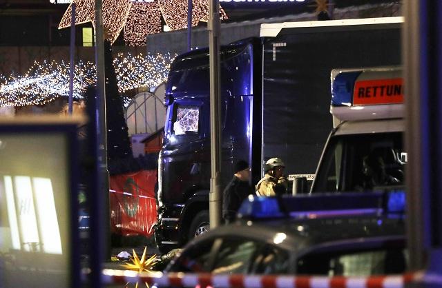 Na archívnej snímke stoja policajti vedľa poškodeného nákladného auta, ktoré vbehlo na preplnené vianočné trhy 19. decembra 2016 v Berlíne