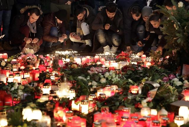 Na archívnej snímke ľudia zapaľujú sviečky neďaleko vianočného, kde sa 19. decembra odohral teroristický útok