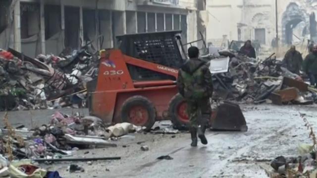 Na snímke z videa sýrski vojaci kráčajú medzi zničenými budovami na ulici v Starom meste Aleppo
