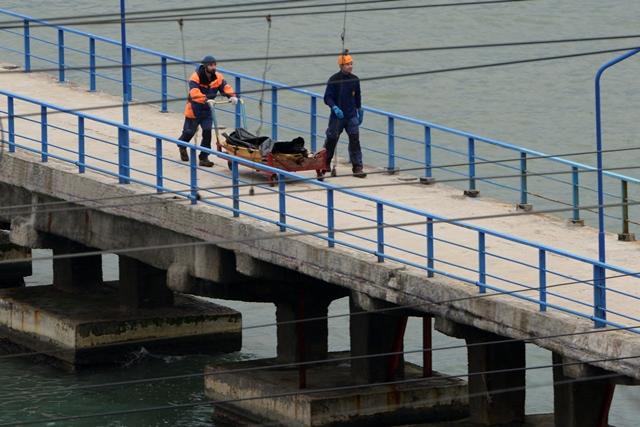 Ruskí záchranári vezú telo z vraku zrúteného lietadla typu Tu-154 na móle neďaleko Soči