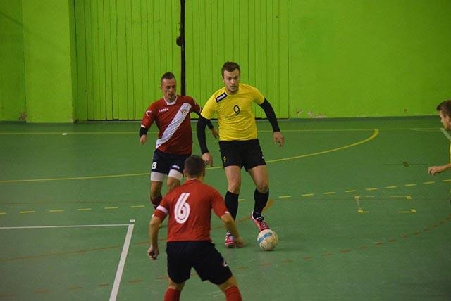 Vsiedmom kole II.ligy vo futsale skupiny Stred 1.FsK Kysucké Nové Mesto zvíťazilo na domácej palubovke nad vedúcom družstvom súťaže Futsal Team Lučenec hladko vpomere 5:2. Na snímke ztohto súboji vidieť domáceho Petra Vavreka (9) vžltom drese pri lopte, ktorého sa snažia oloptu odzbrojiť dvojica futsalistov zLučenca vľavo stojaci Juraj Kuhajdík (13) achrbtom otočený kapitán družstva Attila Fehérvári (6).