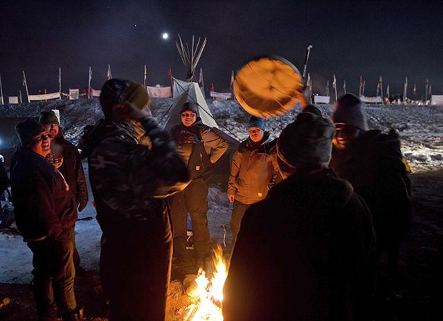 Pôvodní americkí obyvatelia  bubnujú a spievajú počas osláv v indiánskom tábore Oceti Sakowin v Cannon