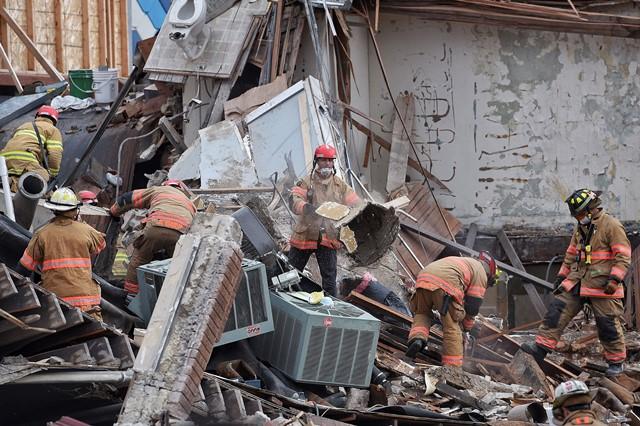 Na snímke záchranári a trosky budovy v meste Sioux Falls
