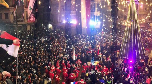Na snímke 13-metrový vianočný stromček v Aleppe a kresťania, ktorí prvýkrát po piatich rokoch môžu sláviť Vianoce.