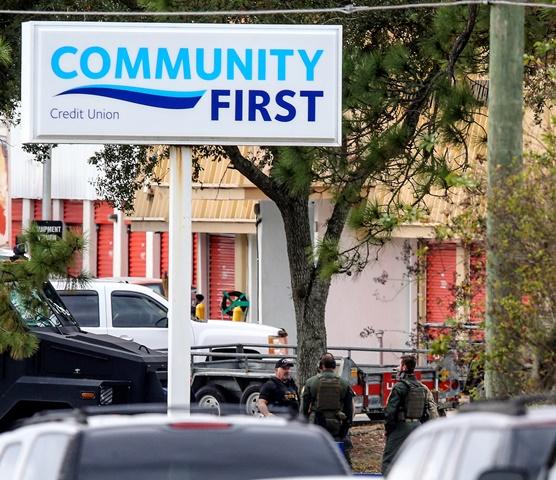 Policajti sú pred bankou Community First Credit Union počas rukojemníckej drámy v meste Jacksonville v americkom štáte Florida