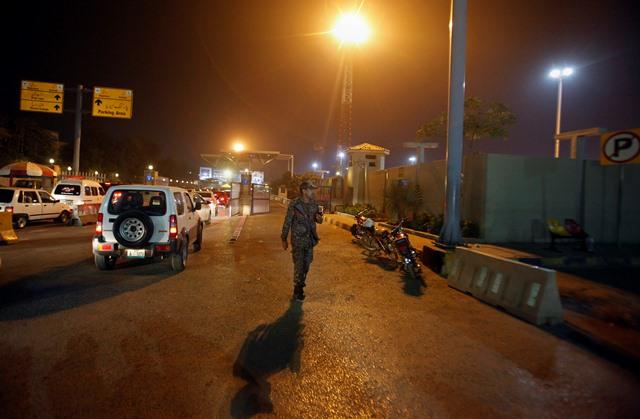 Na snímke bezpečnostný pracovník letiska hliadkuje po havárii lietadla pri vstupe na medzinárodné letisko Benázír Bhuttovej v Islamabade