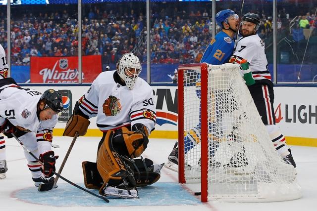 Brankár Chicaga Corey Crawford sa pozerá na puk za bránkovu čiarou po dorážke hráča Blues Patrika Berglunda (druhý sprava) v tradičnom zápase zámorskej NHL Winter Classic St. Louis Blues - Chicago Blackhawks