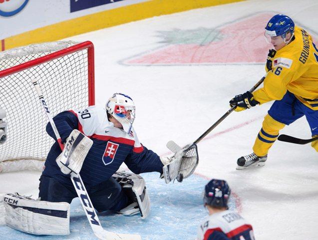 Slovenský brankár Adam Húska chytá strelu Švéda Carla Grundströma vo štvrťfinále MS hokejistov do 20 rokov Švédsko - Slovensko