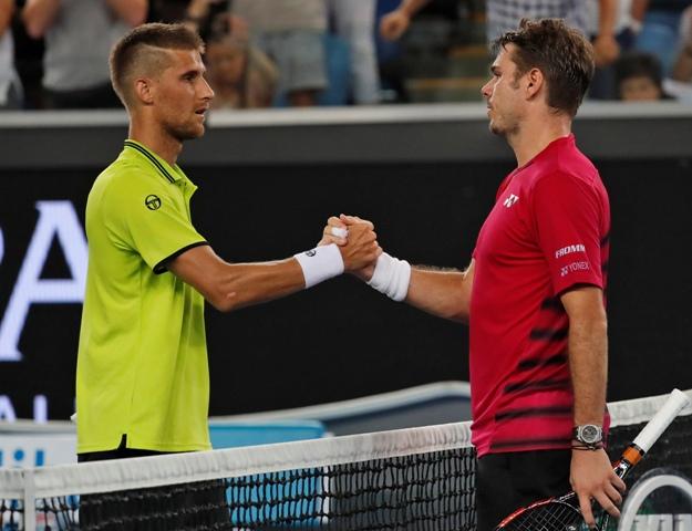 Švajčiarsky tenista Stan Wawrinka (vpravo) si podáva ruku s porazeným Slovákom Martinom Kližanom po jeho výhre v prvom kole tenisového grandslamového turnaja Australian Open v Melbourne