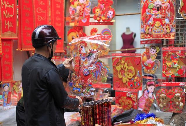 Na snímke muž si prezerá dekorácie s motívom kohúta v starej štvrti vietnamskej metropoly Hanoja 26. januára 2017.  Čínsky lunárny nový rok sa začína 28. januára 2017 a bude sa niesť v znamení ohnivého kohúta