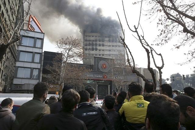 Horiaca ikonická výšková budova Plasco v iránskej metropole Teherán, kde vo štvrtok 19. januára 2017 množstvo hasičov bojovalo s požiarom, sa zrútila. Nie je ešte známe, či niekto pri páde stavby utrpel zranenia. Informovala o tom iránska štátna televízia. V budove sa nachádzalo veľké nákupné centrum. Na snímke Iránčania sledujú dym z horiacej ikonickej výškovej budovy Plasco v Teheráne
